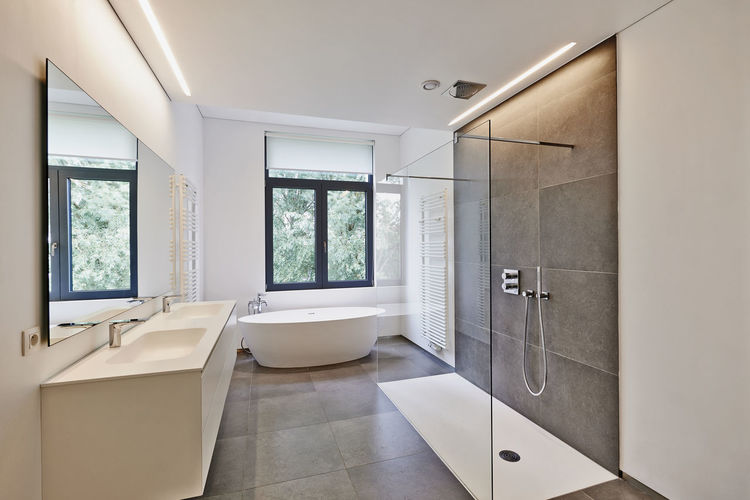 Bathtub in corian, Faucet and shower in tiled bathroom with windows towards garden Architecture Bathroom Bathroom Sink Day Domestic Bathroom Domestic Room EyeEmNewHere Home Interior Home Showcase Interior Indoors  Luxury Modern No People Shower Window