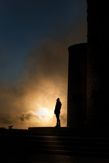 Silhouette woman standing by castle against sky during sunset