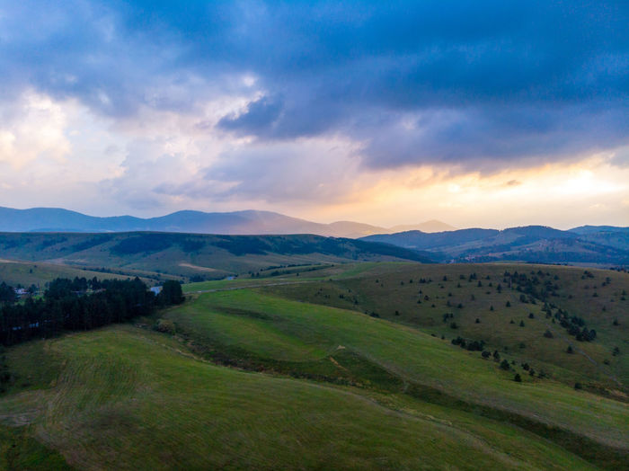 Dramatic Sky Beauty In Nature Cloud - Sky Dronephotography Environment Field Grass Green Color Idyllic Land Landscape Mountain Mountain Range Nature No People Non-urban Scene Outdoors Plant Rolling Landscape Rural Scene Scenics - Nature Sky Tranquil Scene Tranquility
