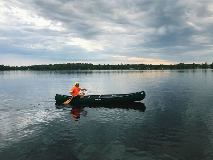 Man sitting in boat on lake against sky
