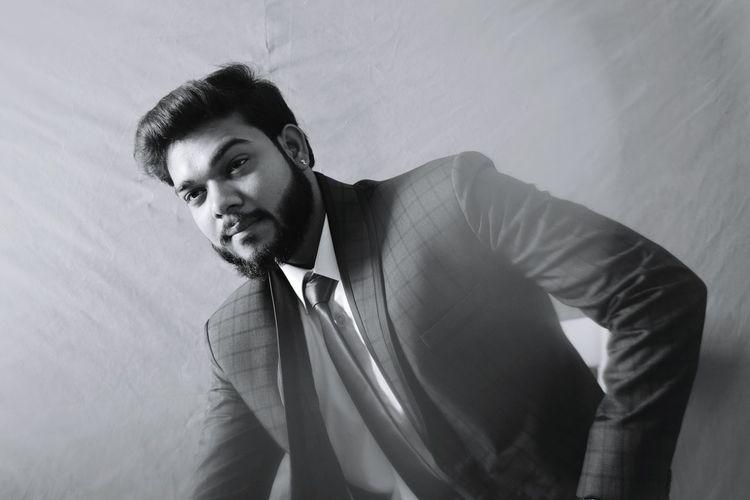 Handsome businessman posing against backdrop in studio