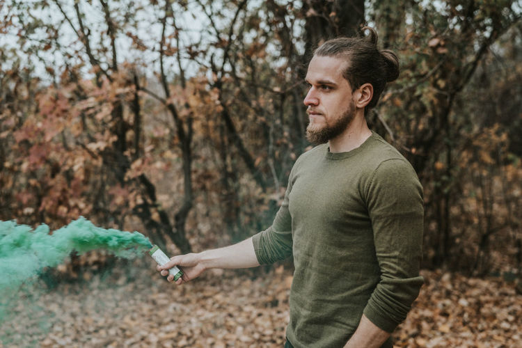 Young man holding distress flare while standing in forest during autumn