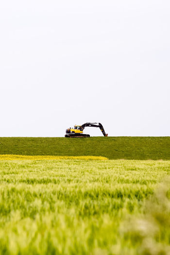Earth mover on grassy field against clear sky