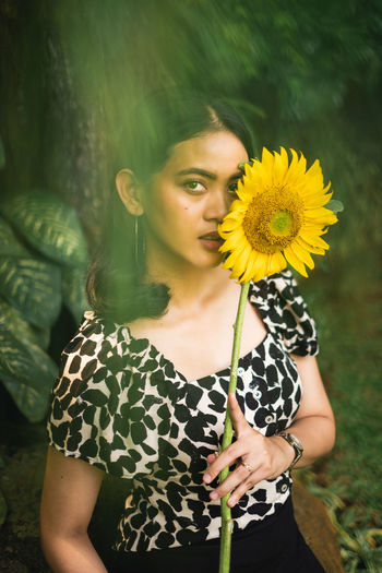 Portrait of woman holding sunflower standing outdoors