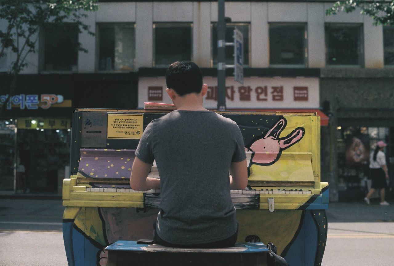 Rear view of street musician playing piano