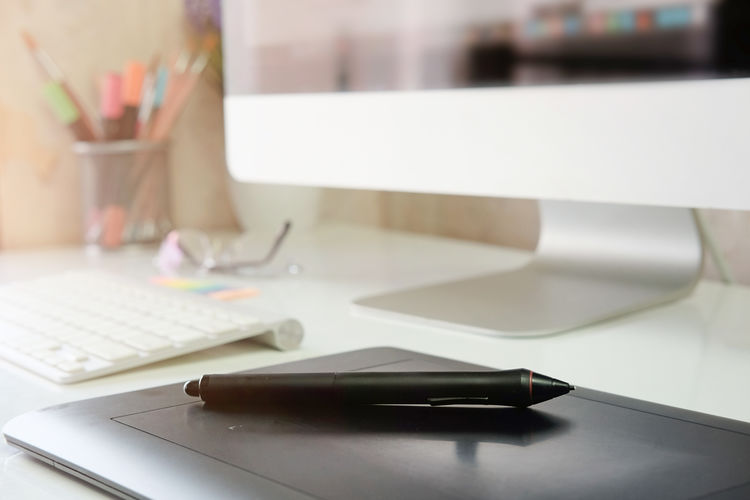 Low angle view of graphics tablet with digitized pen on desk in office