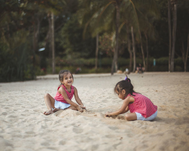 Twins sisters playing on sand at beach
