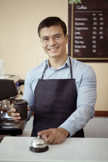 Portrait of smiling man standing in cafe