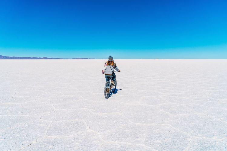 Man with umbrella on desert against blue sky