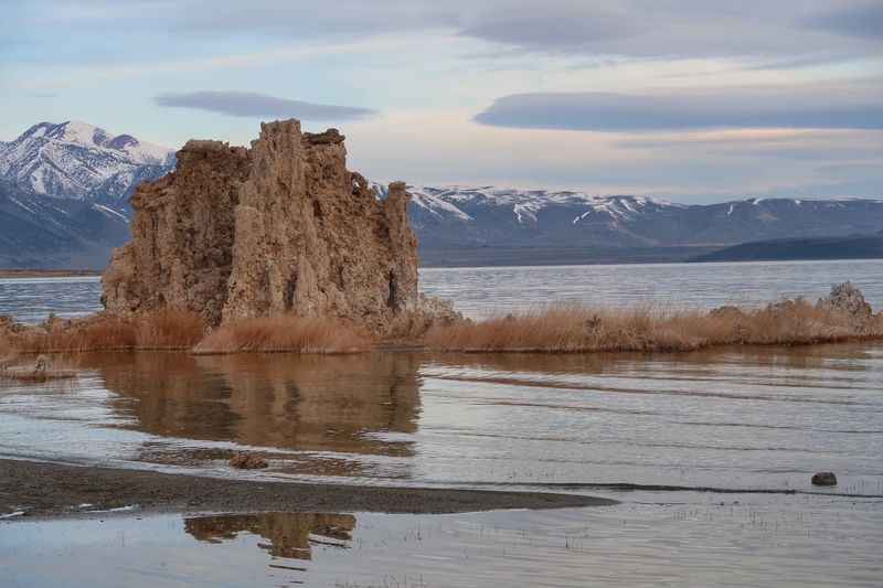 Landscape of large tufa formations in Mono Lake with mountains in the background Tufa Mono Lake Water Sky Cloud - Sky Nature Sea Scenics - Nature Beauty In Nature Reflection Day No People Motion Beach Land Outdoors Waterfront Tranquility Rock Tranquil Scene