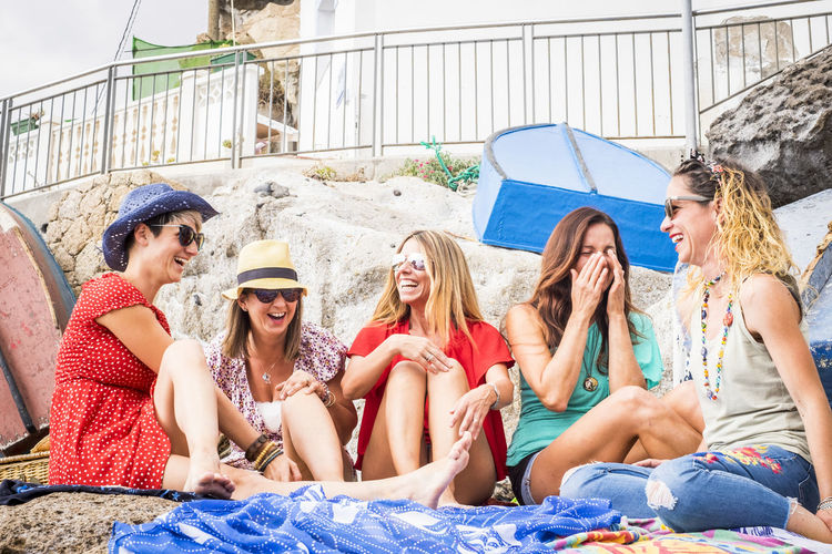 Happy friends talking while sitting at beach