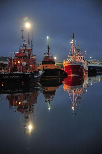 Illuminated ship moored at harbor against sky at night