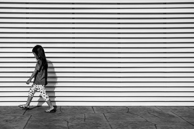 The boring of city life City Life City Street Day Full Length Long Hair Looking Down Monotonous One Girl Only One Person Outdoors Pattern People Real People Side View Stripes Pattern Walk Welcome To Black TCPM
