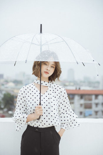 Young woman with umbrella standing on terrace