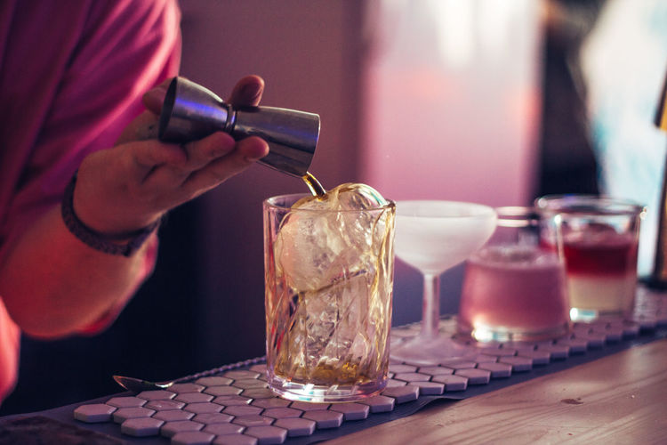 Cropped hand of person pouring alcohol in glass at bar counter
