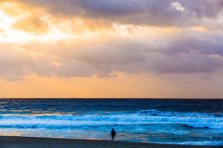 Woman fishing on scenic sea against sky during sunset