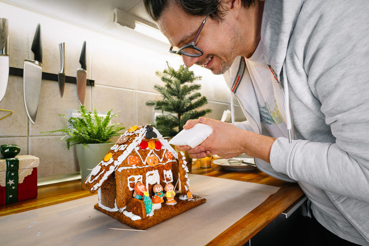 Man preparing gingerbread house in kitchen at home