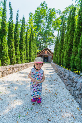 cute children stand and smile with tree background Childhood Child One Person Full Length Females Girls Plant Looking At Camera Standing Tree Day Women Nature Front View Casual Clothing Portrait Smiling Green Color Innocence Outdoors