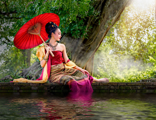 Young Woman With Umbrella Sitting By Lake In Forest