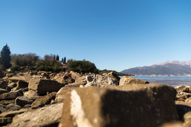 Scenic view of rocks against clear blue sky