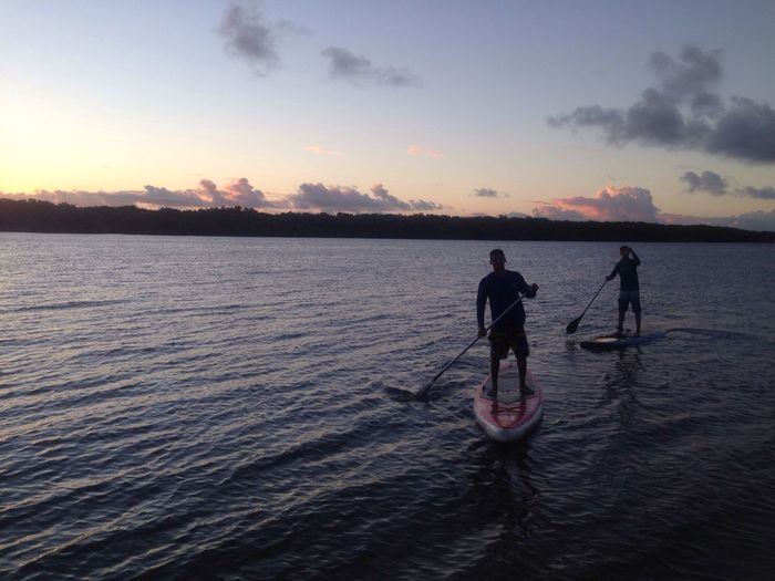 Silhouette people paddleboarding in river against sky at dusk