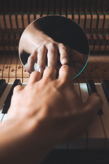 Cropped hand playing piano with reflection on mirror