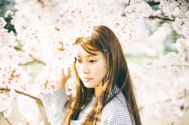 Thoughtful young woman by flowering tree at park