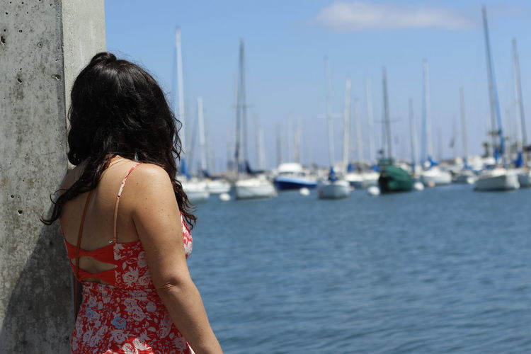 Rear view of woman standing at harbor
