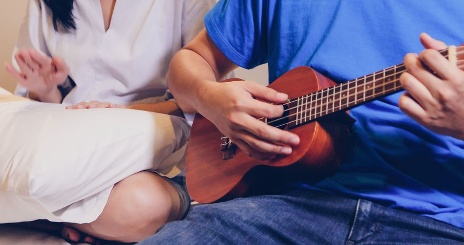 Midsection of man playing ukulele while sitting with female friend on seat