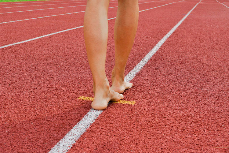 Low section of woman standing on sports track