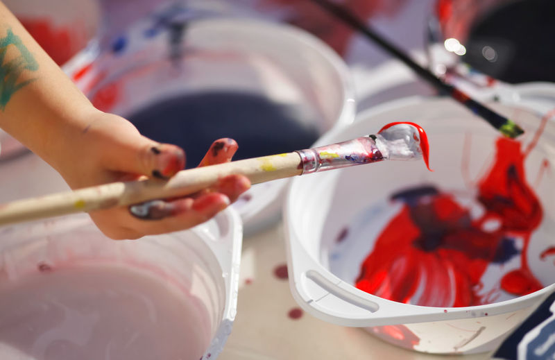 Close-up of girl hand holding paintbrush