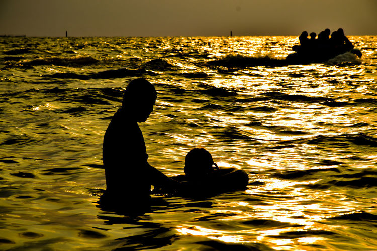 Silhouette people swimming in sea during sunset
