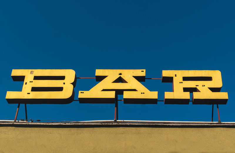 Low angle view of yellow sign against blue sky