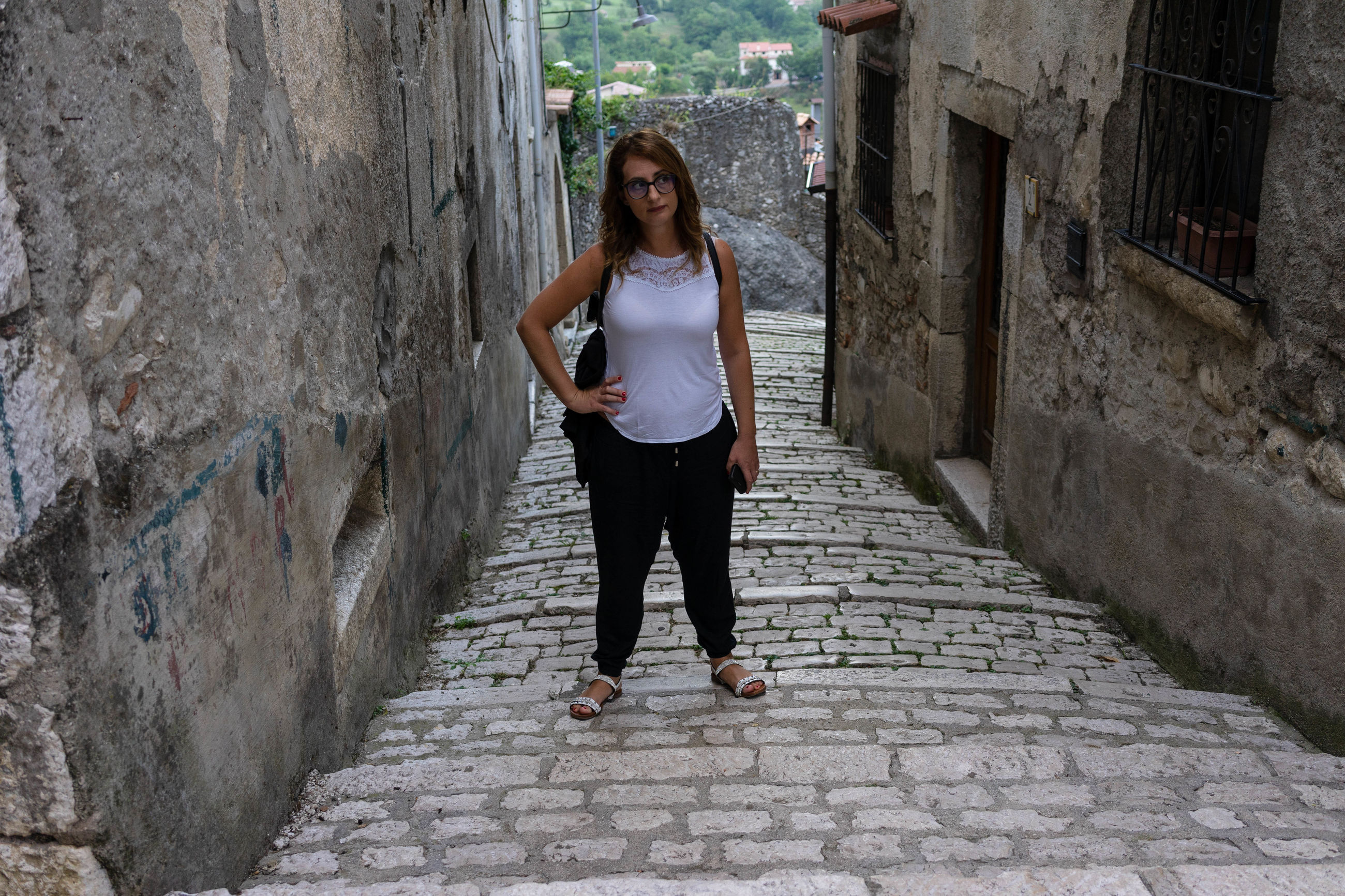architecture, front view, one person, built structure, full length, young adult, building exterior, looking at camera, portrait, casual clothing, lifestyles, wall - building feature, real people, day, footpath, leisure activity, standing, young women, outdoors, hairstyle, beautiful woman, alley