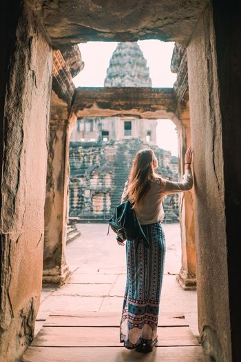 Rear view of woman standing on doorway of ancient temple