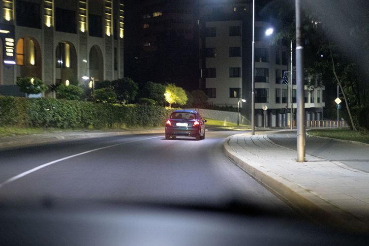 Car on street against illuminated buildings in city