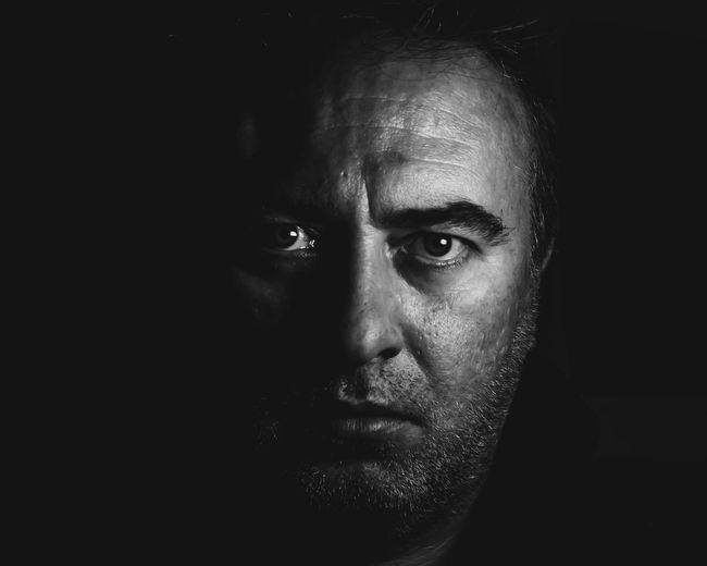 Close-up portrait of serious mature man against black background