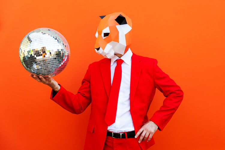 Low angle view of person standing against orange background