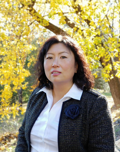 Portrait of beautiful businesswoman standing against trees
