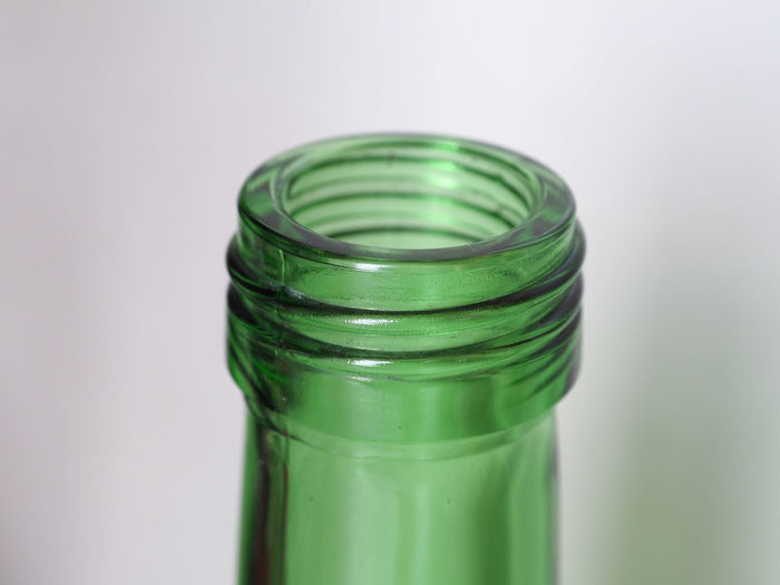 Close-up of green jar on table against white background