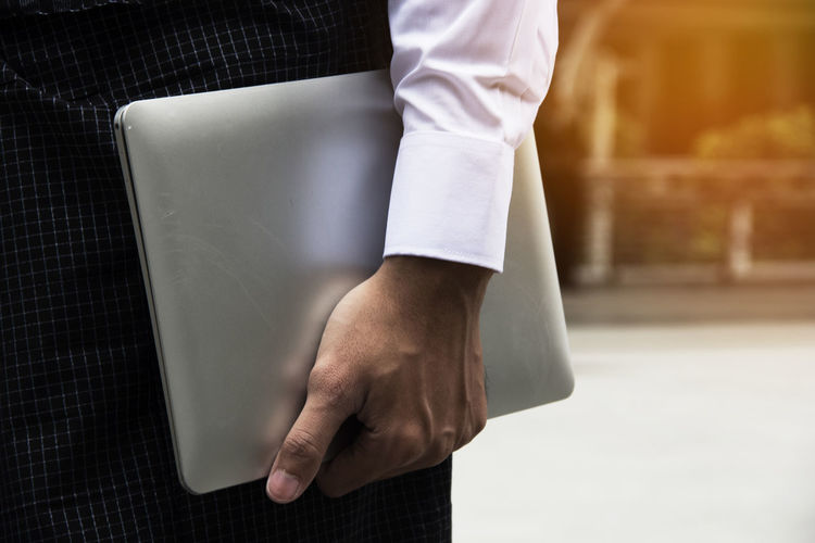 Midsection Of Businessman Holding Laptop While Standing Outdoors