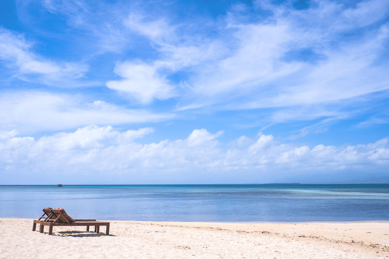 Lounge chairs at beach against cloudy sky