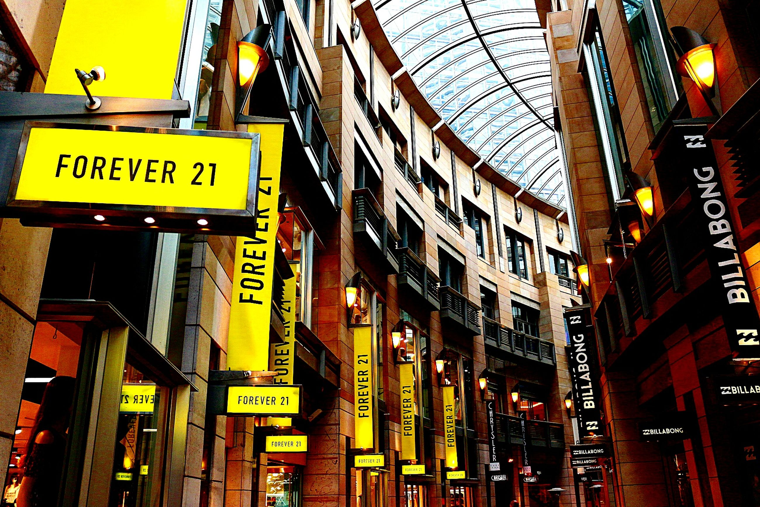 text, western script, communication, architecture, built structure, information sign, city, building exterior, illuminated, sign, road sign, guidance, low angle view, non-western script, yellow, information, arrow sign, neon, variation, shop, skyscraper, commercial sign, advertisement, outdoors, signboard, urban skyline, city life