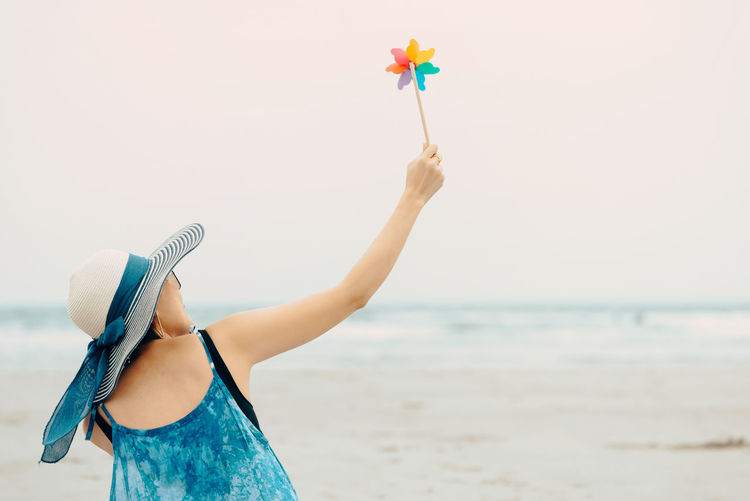 Rear view of woman holding pinwheel toy at beach against sky