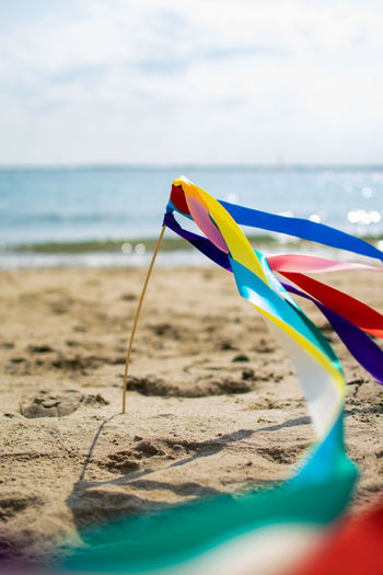 Scenic view of beach against sky with ribbons swaying in a wind.