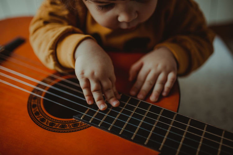 Midsection of child playing guitar at home