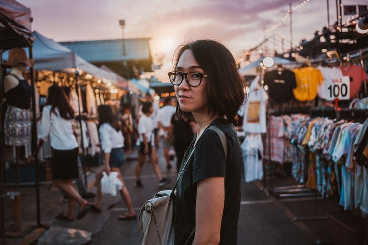 Portrait of young woman standing in city