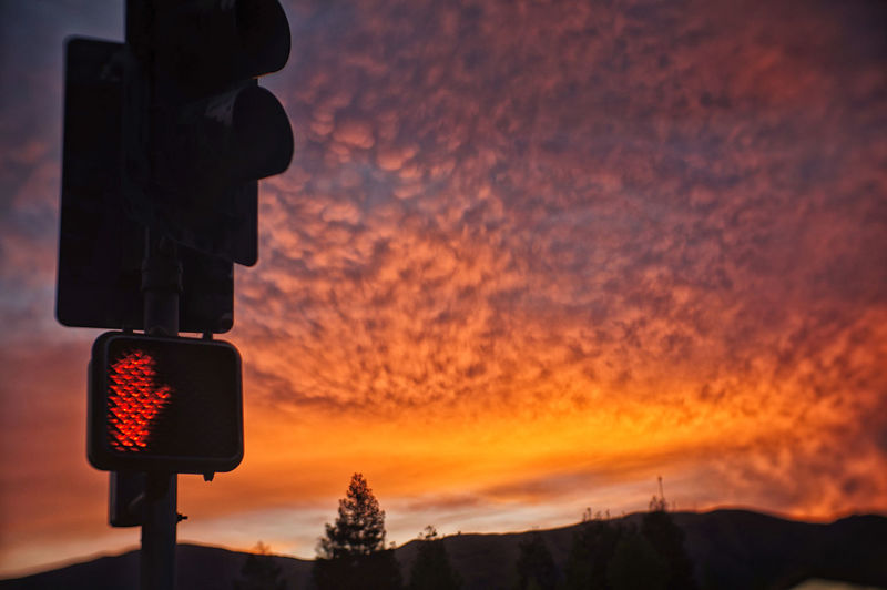 Low angle view of traffic signal against scenic sky