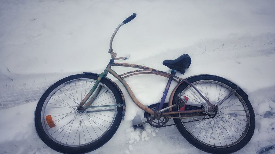 Bicycle parked on snow covered field