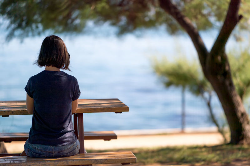 Rear view of woman sitting on picnic table